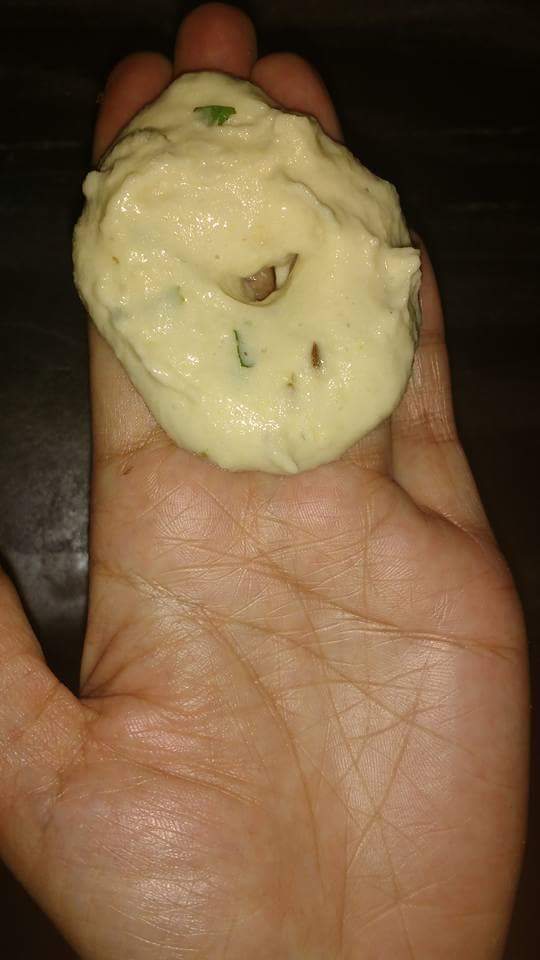 Now apply water on your hand and take batter on your hand and add cashews and raisins in it and make hole as shown in pic