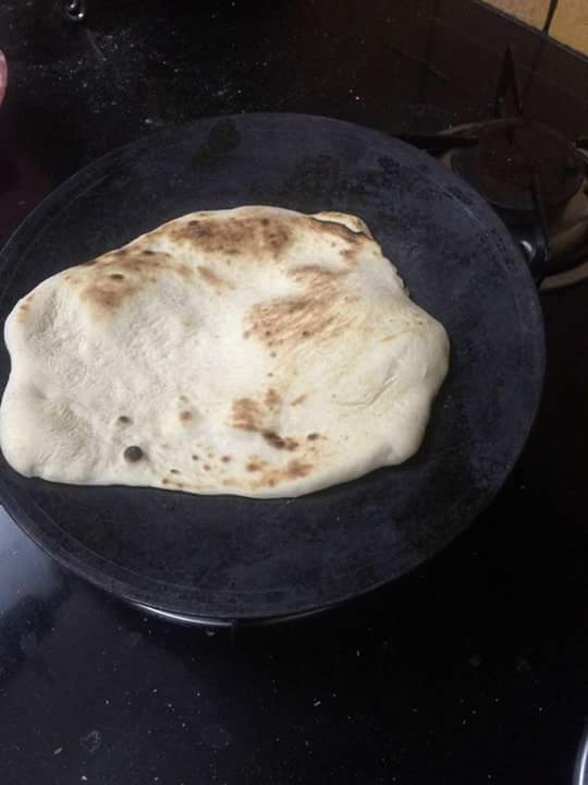 Rotate the tava form all sides so that so naan gets heated properly.