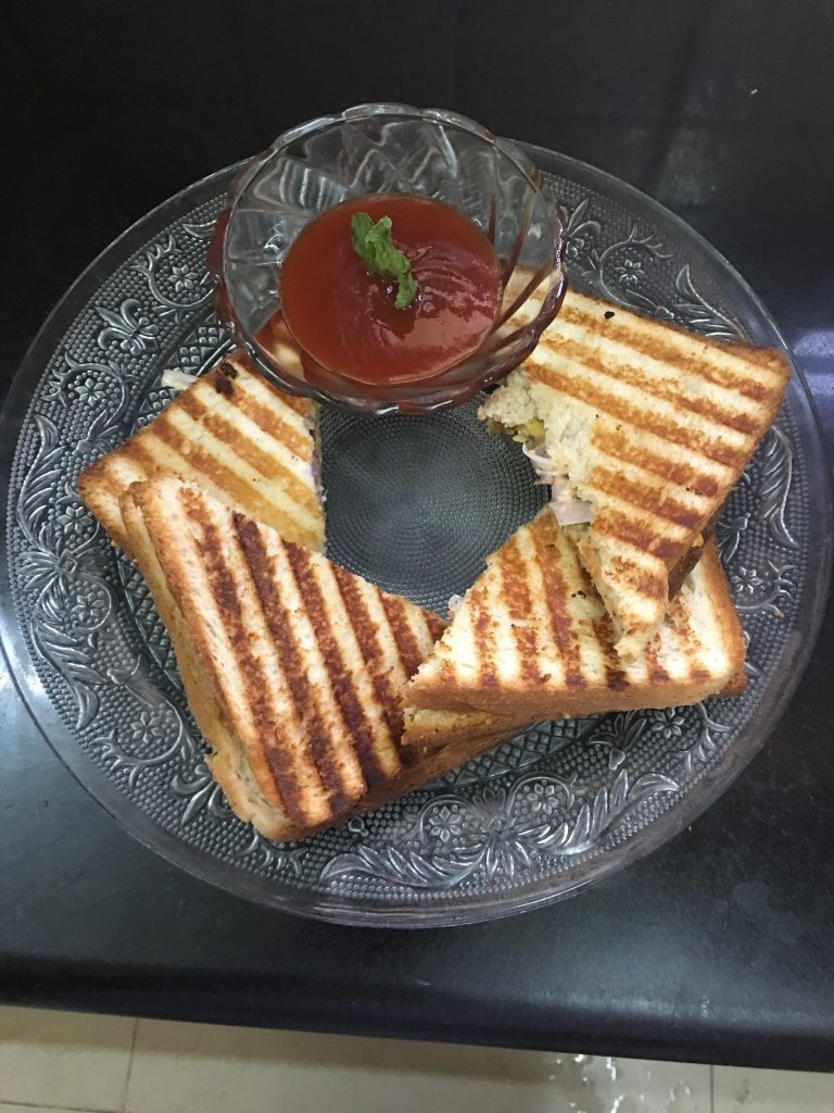 Serve the grill sandwich hot with tomato ketchup and coriander chutney.