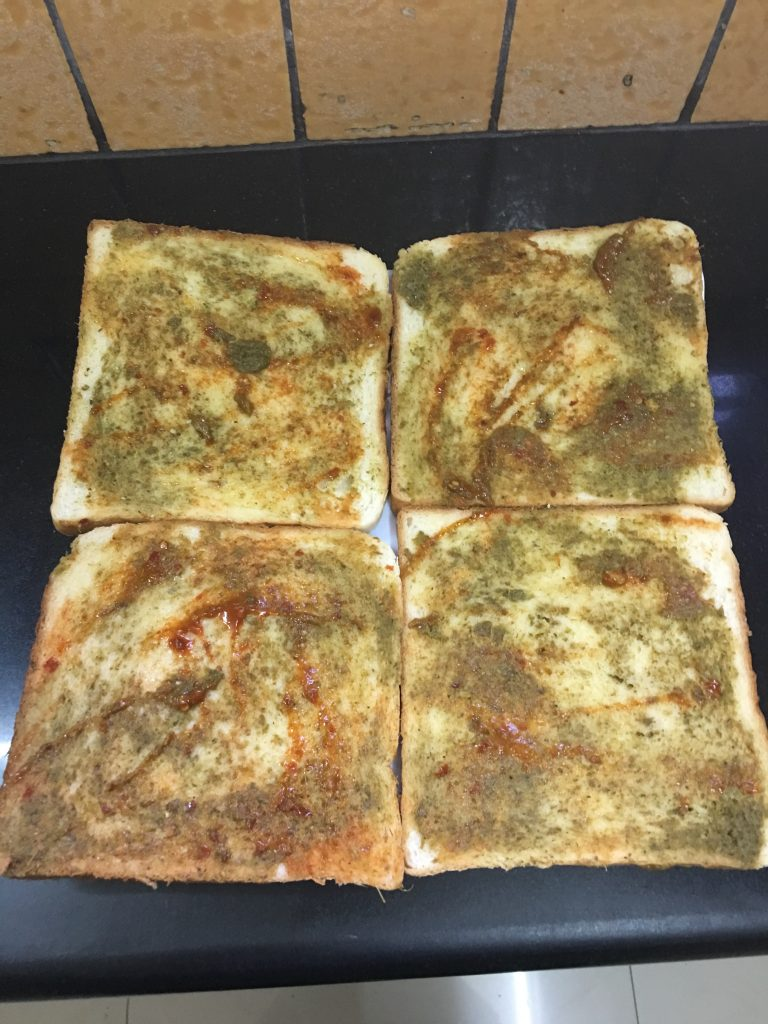 Apply some yellow butter on the bread slice. Then apply green chutney, apply tomato sauce and keep aside.