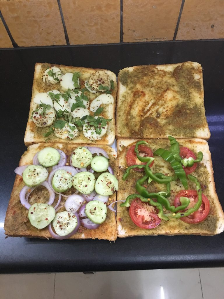 On other slice, arrange cucumber, onion, slices over it and again sprinkle some sandwich masala evenly over it (4th slice). Now keep the buttered side of bread downwards.