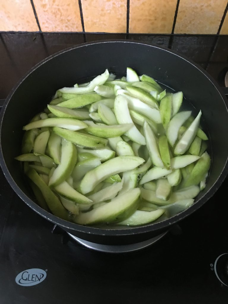 Take a pan and add a half pan of water, raw mangoes slices, ginger in it.