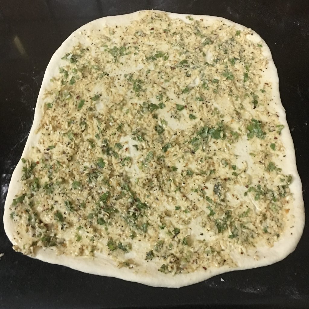 Now the 2-3 tbsp butter mixture on the dough, then sprinkle some grated cheese.