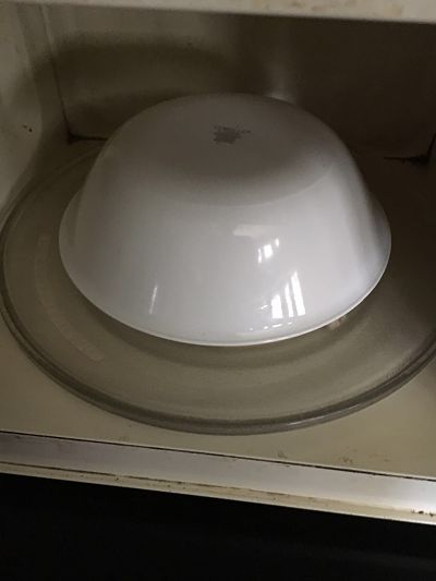 Place the plate in the microwave and cover it with a big bowl , inverted on the plate. Make sure it is microwaveable.